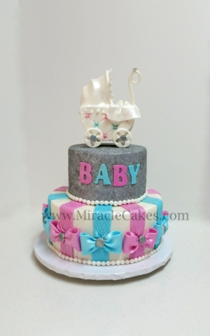 Baby shower cake with a baby carriage topper.