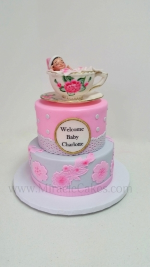 Baby shower cake with a baby in a tea cup topper