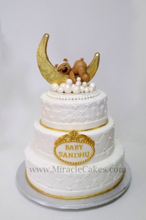 White and Gold theme baby shower cake with a sleeping baby bear figurine
