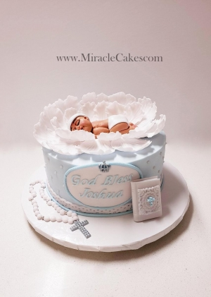 Christening cake with a handcrafted baby topper.