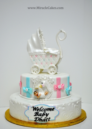 Pink and Blue baby shower cake with a carriage topper